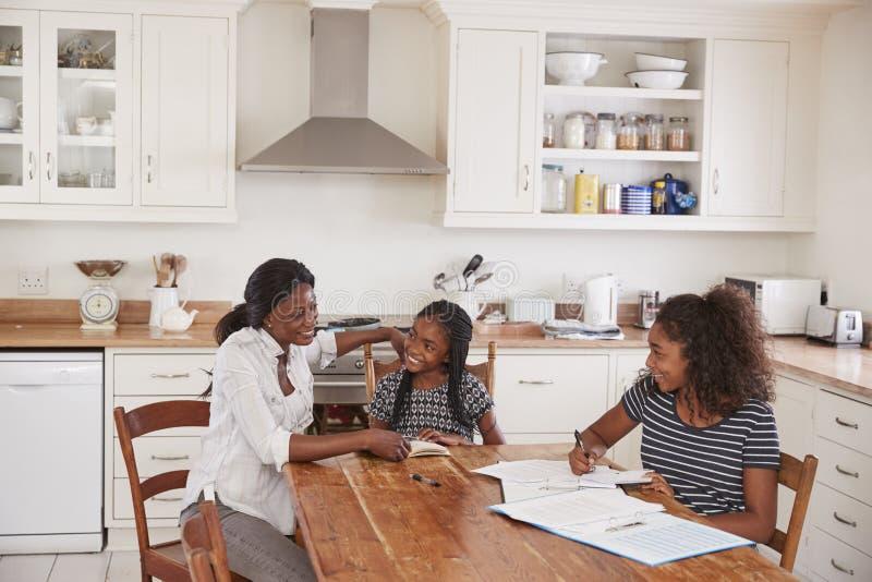Mutter, die zwei Töchtern bei Tisch sitzen hilft, Hausarbeit tuend lizenzfreie stockfotografie