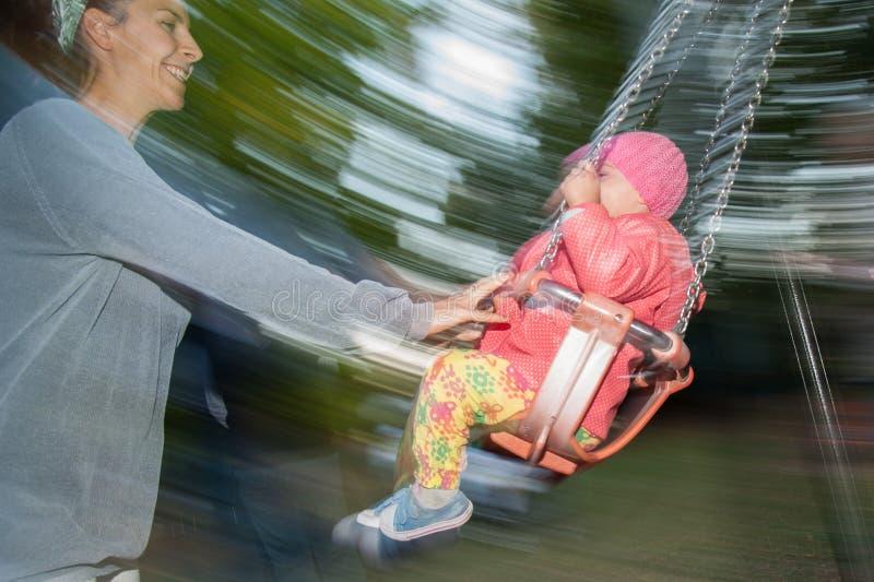 Mutter drückt das Kind auf dem Schwingen lizenzfreie stockbilder