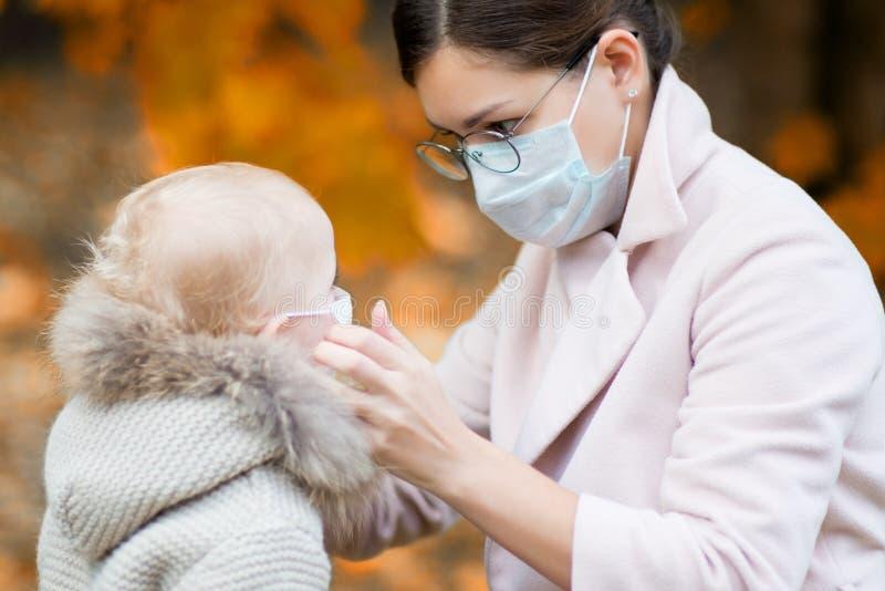 Mutter in einer medizinischen Gesichtsmaske passt die ärztliche Maske an ihre kleine Tochter an, die im Herbst im Hof sitzt stockbilder
