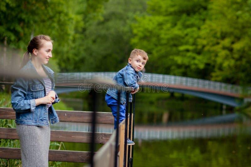 Mutter erfährt, dass das Kind in das Wasser fällt Ein kleiner Junge klettert ein Br?ckengel?nder im Park Die Drohung von lizenzfreies stockbild