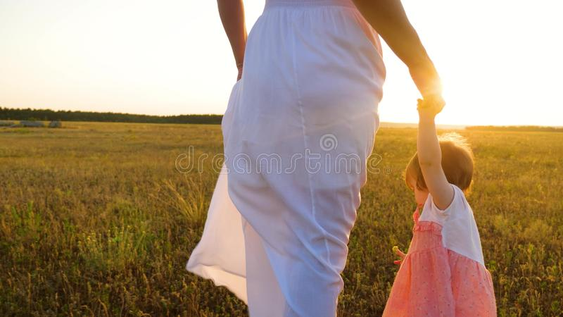 Mutter geht mit ihrer kleinen Tochter und hält Baby eigenhändig Glückliche Familie, die im Park im Sommer in den Strahlen vom war stockfoto