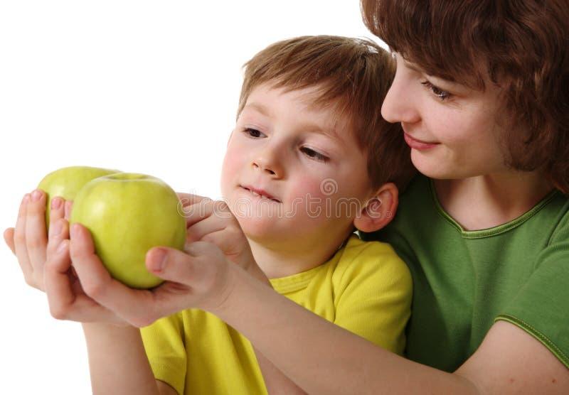Mutter gibt Sohn einen Apfel stockfotografie