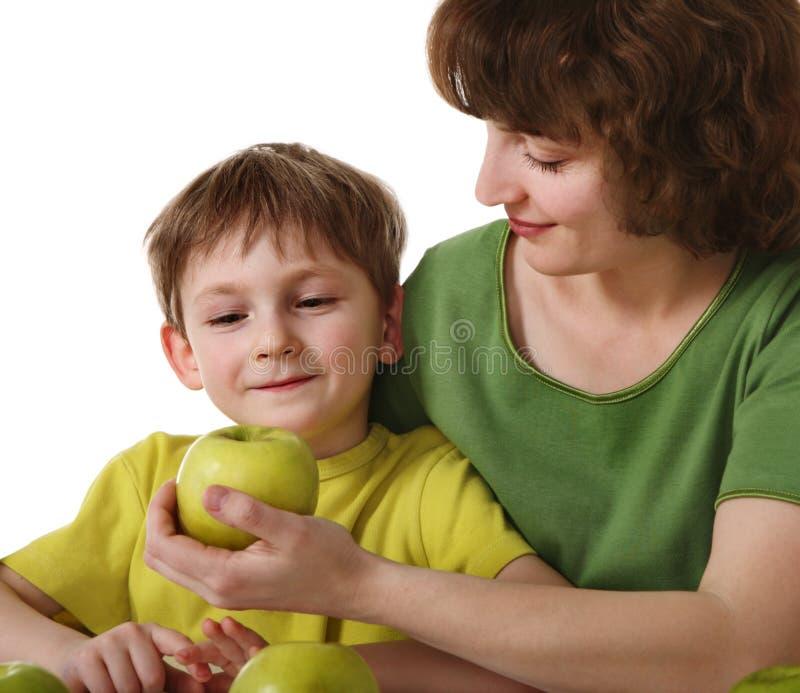 Mutter gibt Sohn einen Apfel stockbild