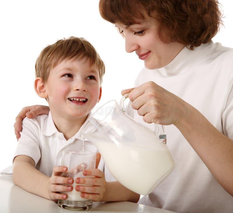Mutter gießt Milch zum Sohn stockbild