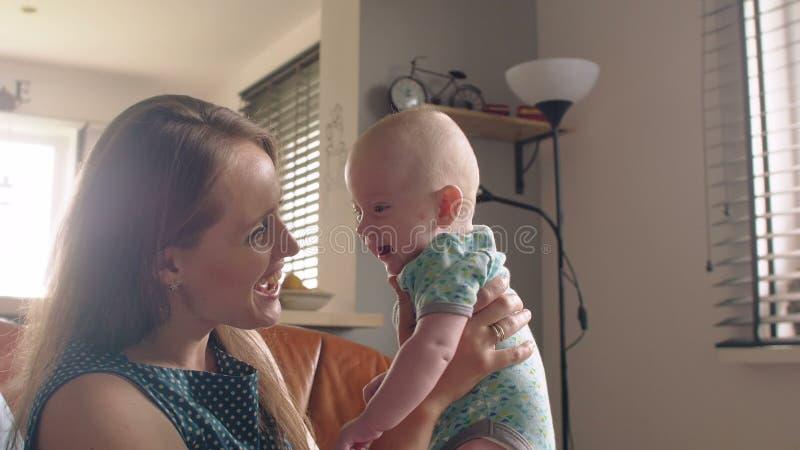 Mutter hält ihr entzückendes lächelndes Baby, das auf dem Sofa sitzt 4K lizenzfreies stockfoto
