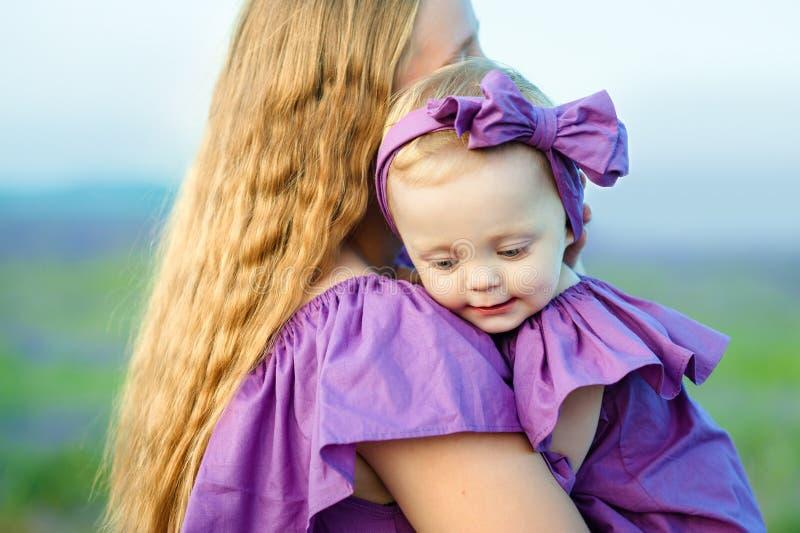 Mutter hält Tochter in ihren Armen und in Spielen auf der Natur Schöne und glückliche Mutter mit ihrem kleinen Mädchen, das drauß stockbild