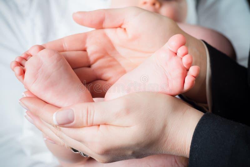 Mutter halten leicht die Füße ihr Kindes stockbild