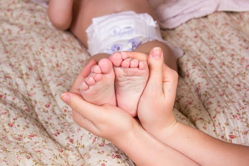 Mutter halten leicht Schätzchenfahrwerkbein in der Hand an Schönes Farbbild mit Weichzeichnung auf Babyfuß stockbild