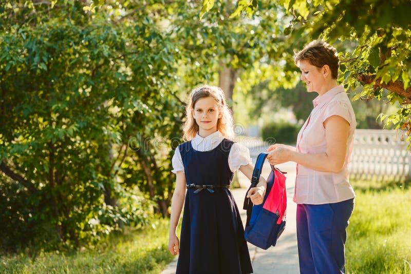 Mutter hilft Tochter, einen Rucksack zu tragen stockfotos