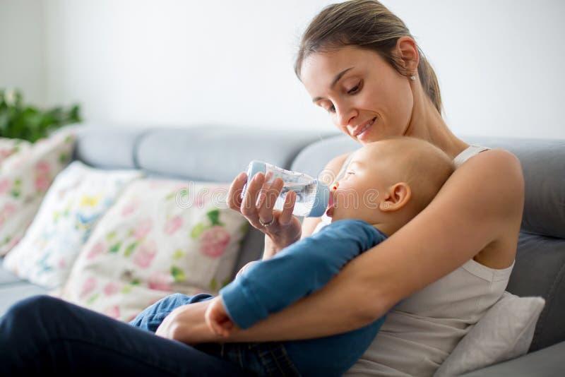 Mutter, ihr Baby von der Flasche einziehend und sitzen auf der Couch a stockfotografie
