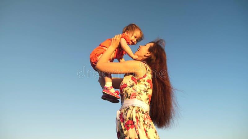 Mutter ihre Tochter bis zum blauen Himmel werfen Zeitlupeschmierfilmbildung Mutter spielt mit kleinem Kind in ihren Armen gegen H lizenzfreie stockfotos