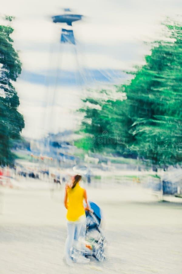 Mutter im gelben Kleid mit Wagen gehend in Bratislava - abstrakter Expressionismus-Impressionismus-Fotografie stockfotos