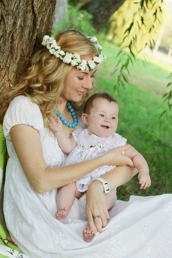 Mutter im Kranz, der lächelndes Baby hält stockbilder