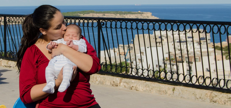 Mutter im roten T-Shirt, das ein altes neugeborenes Baby des Monats hält lizenzfreie stockfotografie