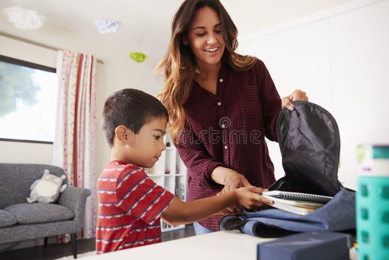 Mutter im Schlafzimmer-helfenden Sohn, zum der Tasche zu verpacken bereit zur Schule lizenzfreies stockbild
