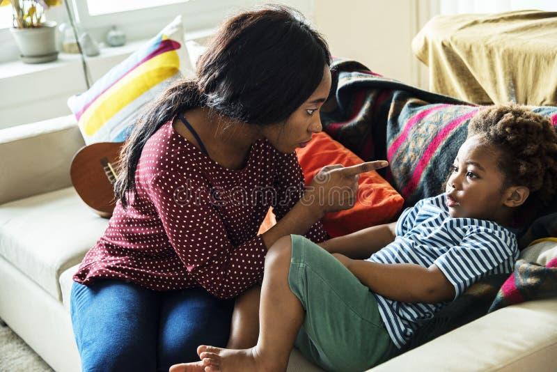 Mutter ist, tadelnd zeigend und ihren Sohn stockfoto