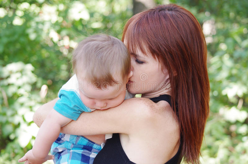 Mutter jubelt oben dem beleidigten Baby zu stockbild