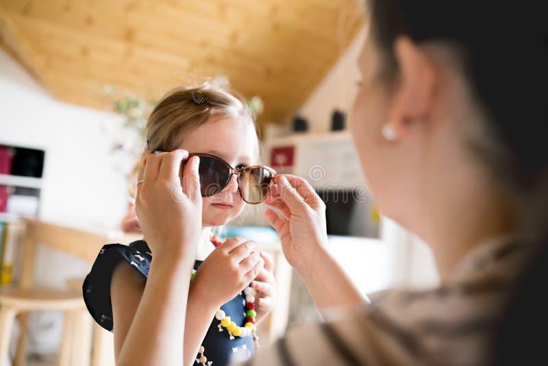 Mutter legt an Sonnenbrille ihrer netten kleinen Tochter vor stockfotografie