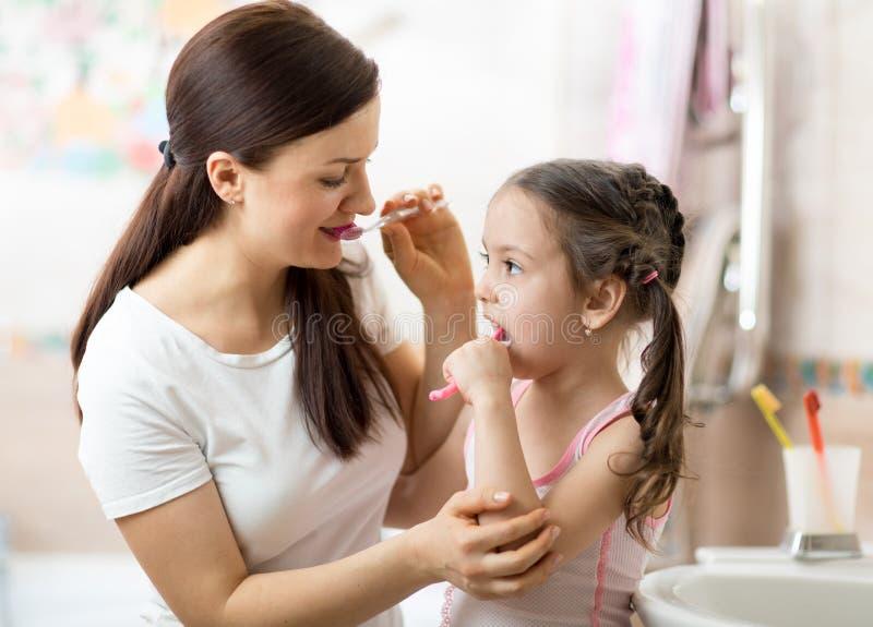 Mutter lehrt ihre kleine Tochter akkurat Zahnputzen lizenzfreies stockbild