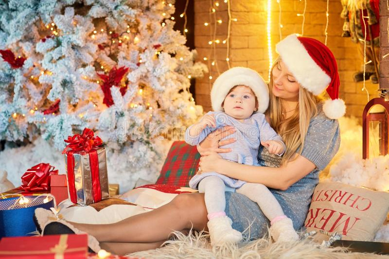 Mutter mit Baby in einem Hut von Santa Claus im Weihnachtsraum stockbilder