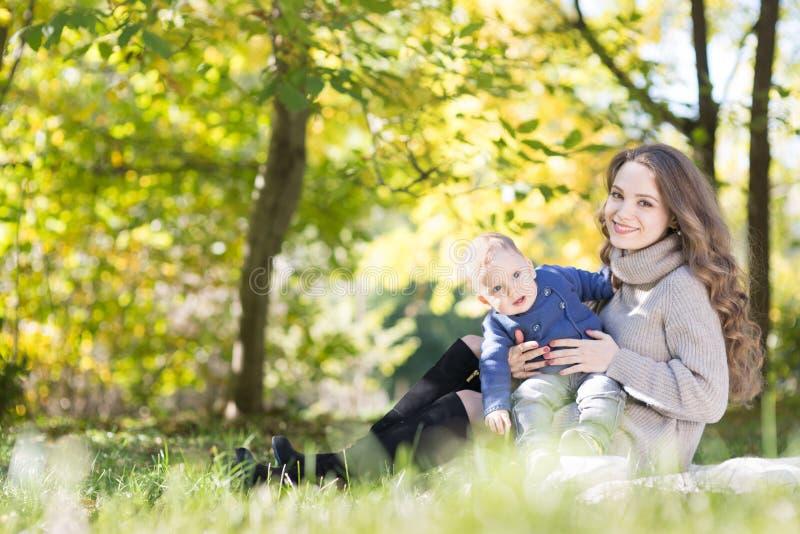 Mutter mit Baby im Herbstpark lizenzfreies stockbild