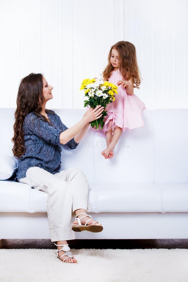 Mutter mit Blumen und Tochter lizenzfreies stockfoto