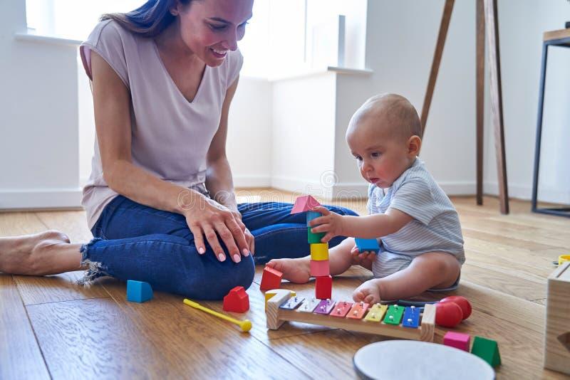 Mutter mit dem Baby-Sohn des achtmonatigen Babys, der durch mit farbigen Holzklötzen zu Hause spielen lernt lizenzfreie stockfotografie