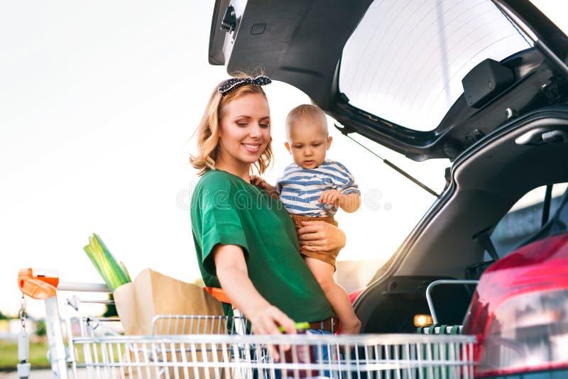 Mutter mit dem Baby, welches das Einkaufen in Rückseite des Autos setzt stockbild