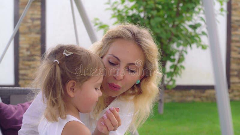 Mutter mit dem blonden Haar wenden Sorgfalt über kleine Tochter an stockfotografie