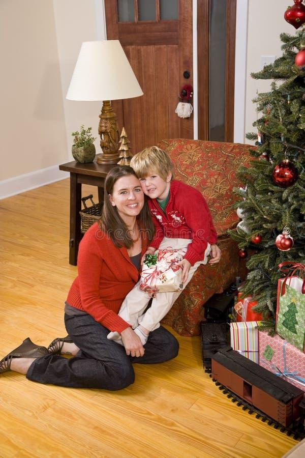 Mutter mit dem Jungen anhalten anwesend durch Weihnachtsbaum lizenzfreie stockfotografie