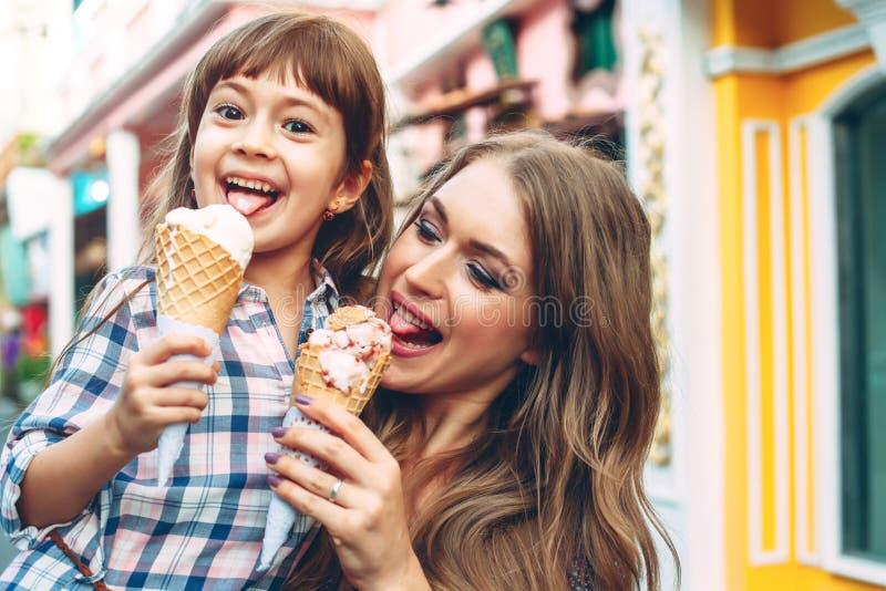 Mutter mit dem Kind, das Eiscreme in der Stadtstraße isst lizenzfreie stockfotos