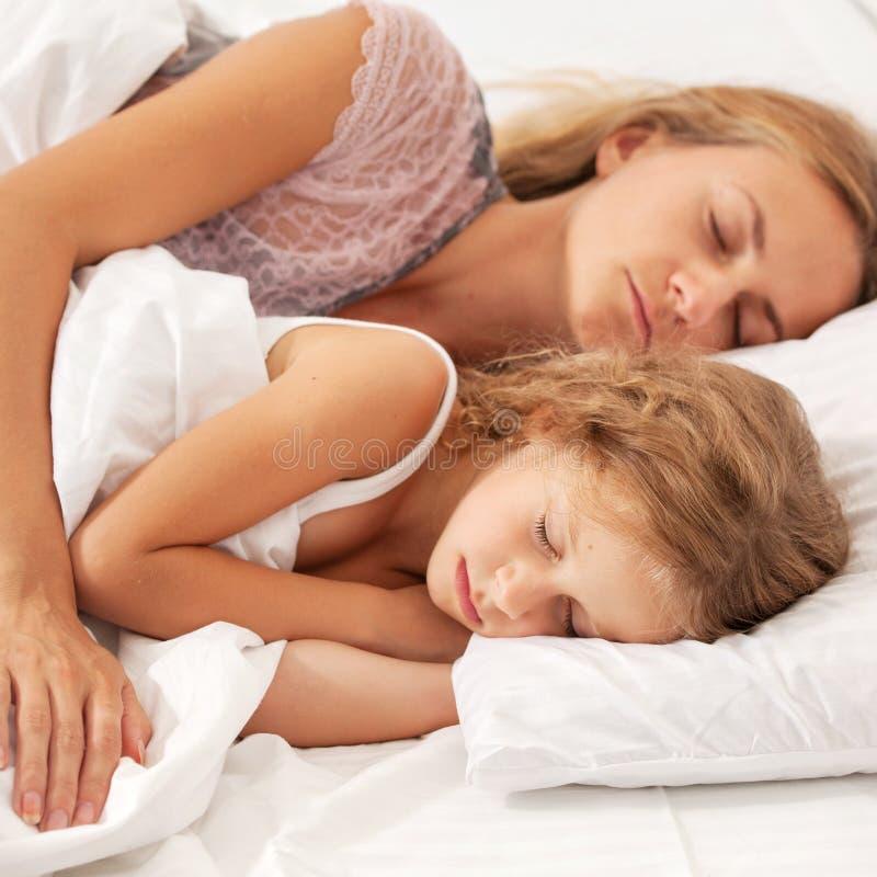 Mutter mit dem Kind, das im Bett schl?ft lizenzfreies stockbild