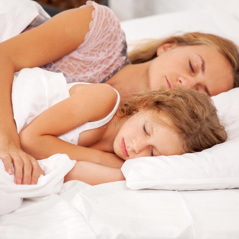 Mutter mit dem Kind, das im Bett schl?ft stockfotografie