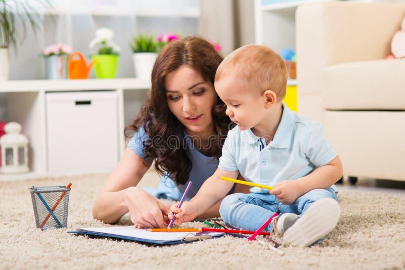 Mutter mit dem Kind, das im Haus spielt lizenzfreies stockfoto