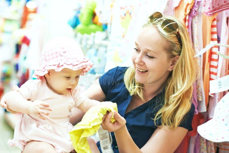 Mutter mit dem kleinen Kind, das Babykleid im Shop wählt stockfotos