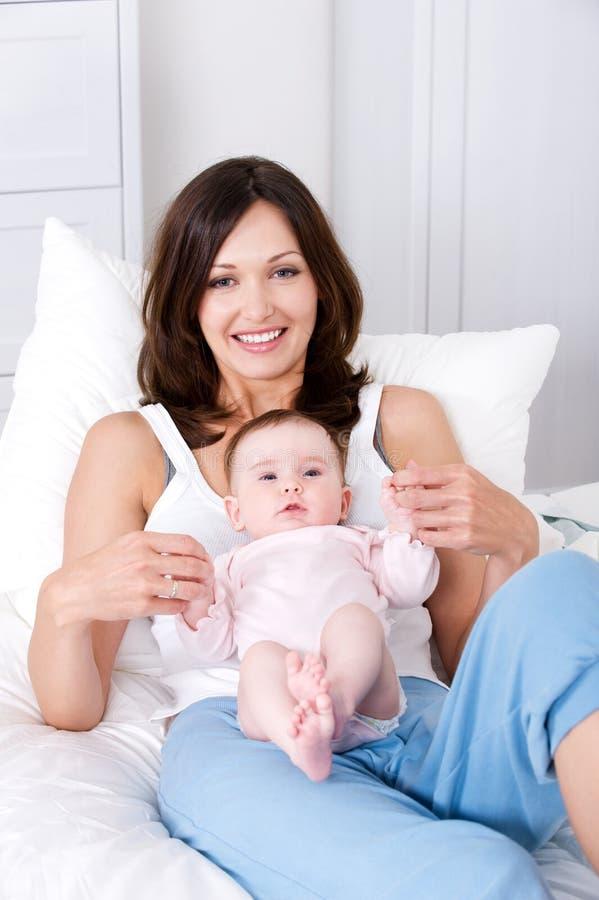 Mutter mit dem Schätzchen, das zu Hause in den casuals sitzt lizenzfreie stockbilder