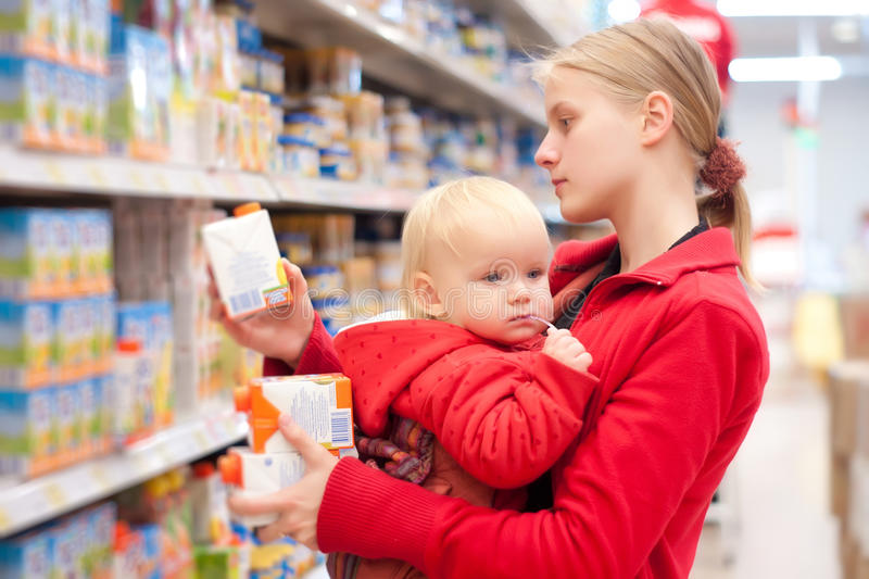 Mutter mit dem Schätzcheneinkaufen im Supermarkt lizenzfreie stockfotos