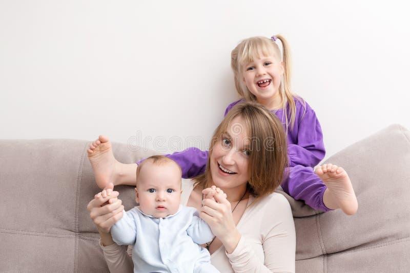 Mutter mit dem Sohn und Tochter, die Spaß auf Sofa haben Lächeln und frohe Naturen Glückliches Familienkonzept stockfoto