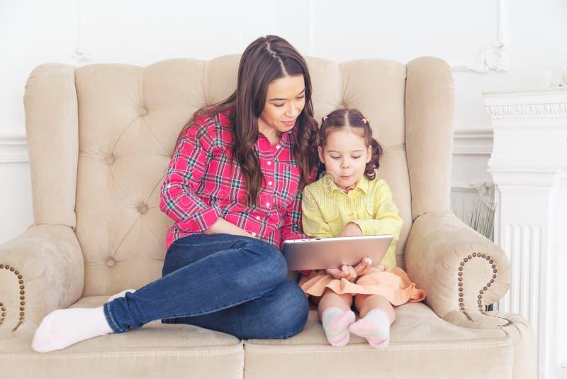 Mutter mit den Kindern, die Computertablette lernen lizenzfreie stockfotografie