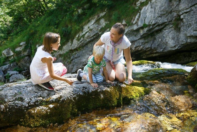 Mutter mit den sprechenden Kindern, Trinkwasser von einem reinen, frischen und kühlen Gebirgsstrom auf einer Familienreise lizenzfreie stockfotos