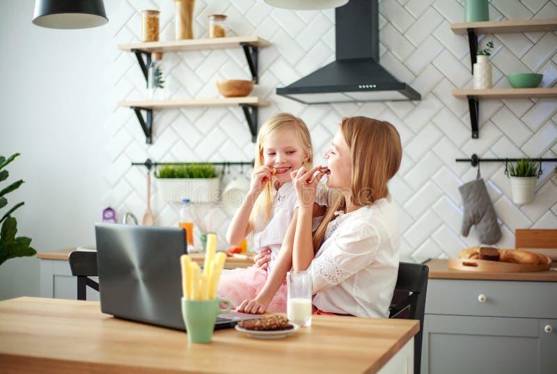 Mutter mit der Babytochter, die bei Tisch mit Lebensmittelgeschäften in der Küche mit Laptop sitzt stockbilder
