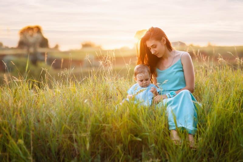 Mutter mit der kleinen Tochter, die auf Wiese sitzt stockfotos