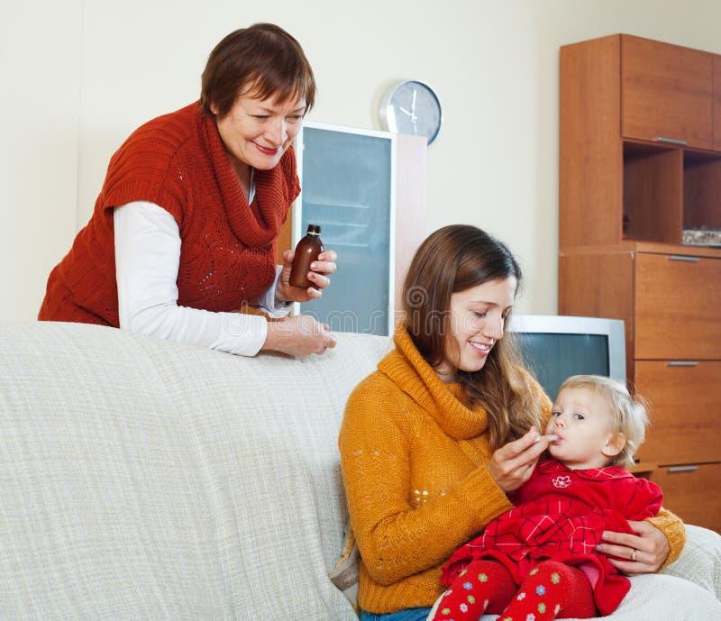 Mutter mit der reifen Frau, die dem unwohlen Baby Medikament gibt lizenzfreies stockfoto