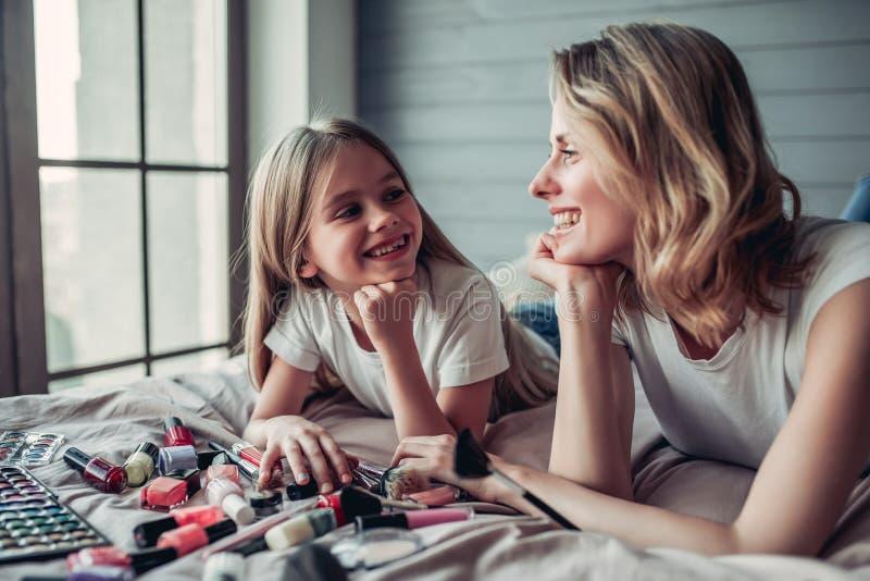 Mutter mit der Tochter, die Make-up tut stockfotos