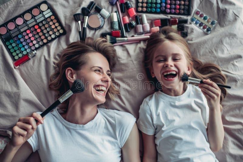 Mutter mit der Tochter, die Make-up tut lizenzfreie stockfotos