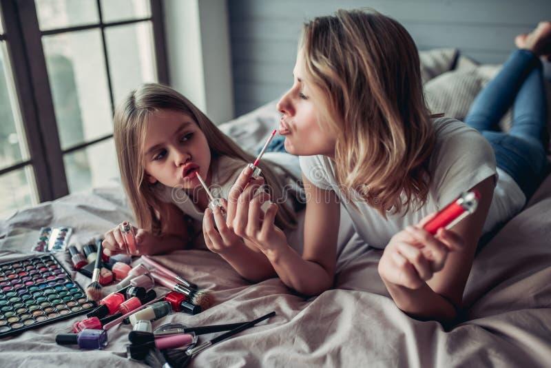 Mutter mit der Tochter, die Make-up tut stockbild