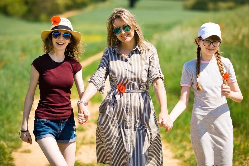 Mutter mit der Tochter, die Mohnblumenblumen hat, gehen auf Wagenstra?e lizenzfreie stockbilder
