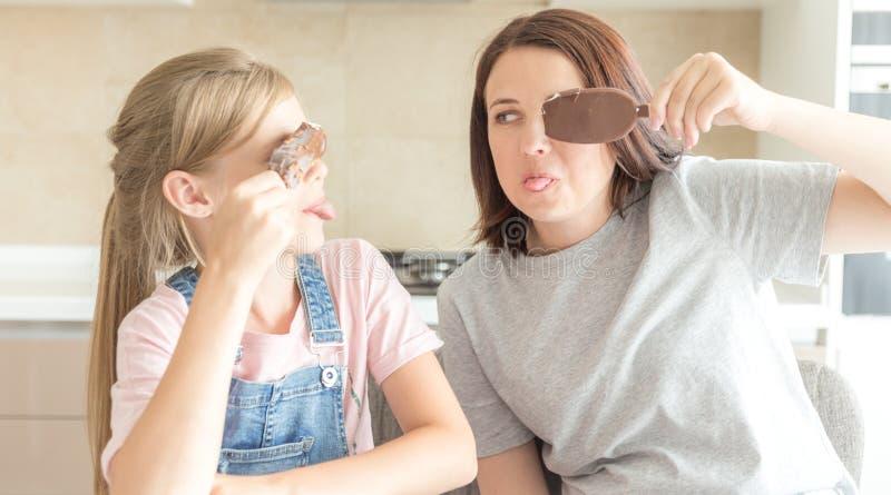 Mutter mit der Tochter in der Küche Eiscreme essend Gute Beziehungen des Elternteils und des Kindes Gl?ckliches Familienkonzept stockfotos