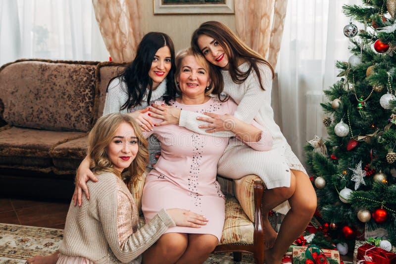 Mutter mit drei schönen Töchtern, die für die Kamera aufwerfen stockfoto