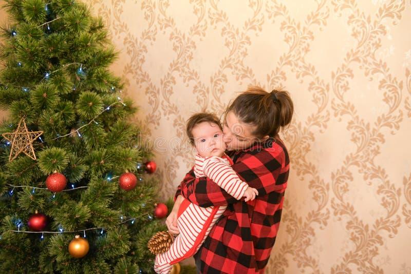 Mutter mit einem Kind in der Nähe des Weihnachtsbaums holt den Baum und bereitet sich auf den Urlaub vor Halblanges Portrait des  stockfotos